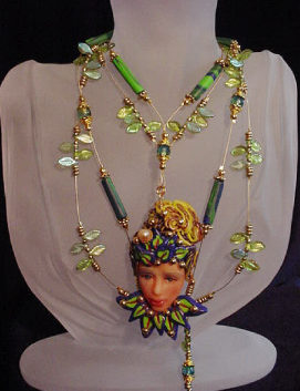 Handcrafted Fairy Face Green Necklace-Handmade with Polymer Clay. Findings, crimps and clasp are 14K gold plated. Gold plated Beadalon .018 in wire is also used. Glass and brass beads are used for final details. Water pearl for final detail. Unique design!