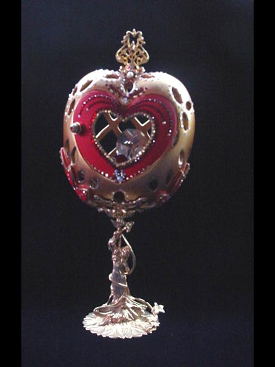 Decorated Egg Heart Jewel-Dimensions: About: 8.5 in h x 4 in w. Description: Front red heart door opens. Inside, one large drop AB Austrian Crystal and red heart shaped crystal, both resting on a red velvet pillow with gold color details. This piece was imperial gold color and red satin finish. Accented with AB Austrian Crystals and red Ruby crystals. 18K gold plated stand and fidings.Decorated box available for this eggypiece.Retail Price: $295.00