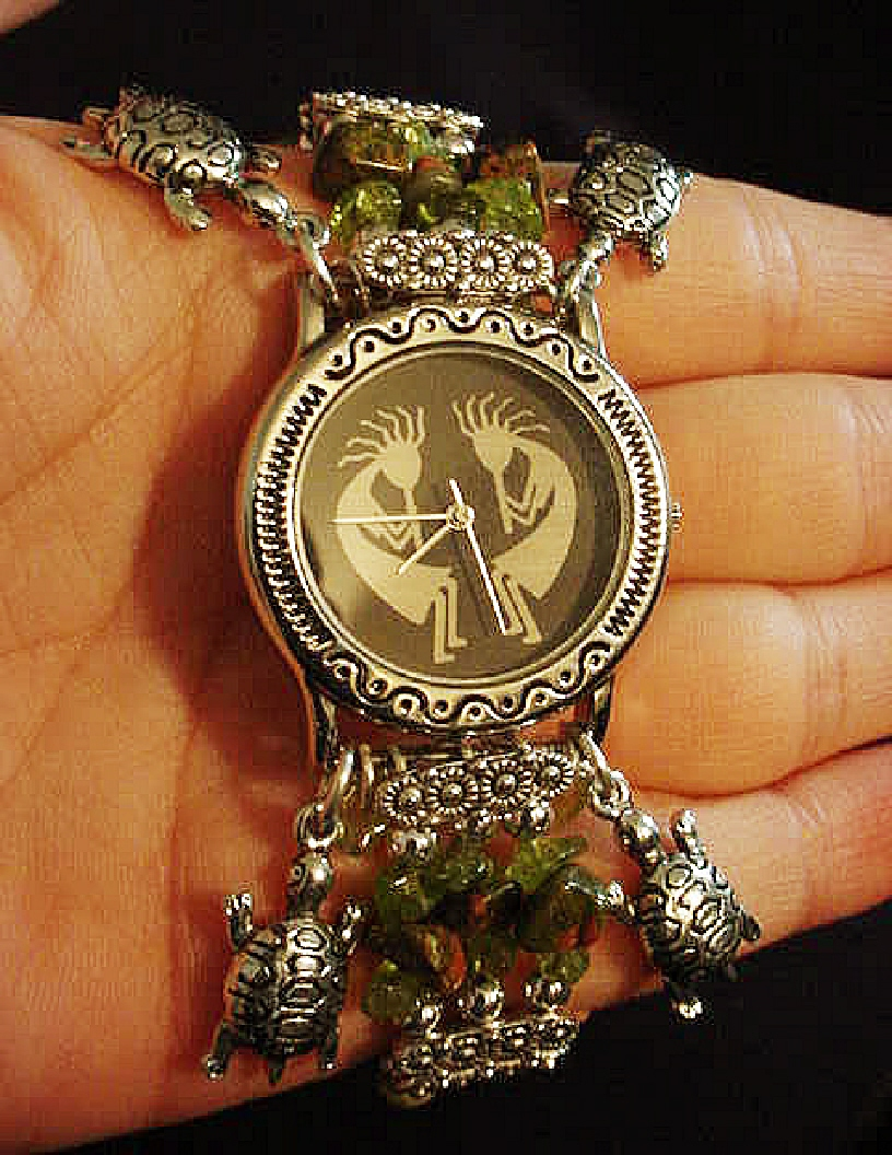 Handcrafted Semi-precious Kokopelli Watch 1- Handcrafted with Semi-precious Unachite and Peridot Stones. Embellished with Silver plated  beads and findings. Five turtle charms are used for final details. Stretch cord is used for watch bands. Round Large Silver watch face.