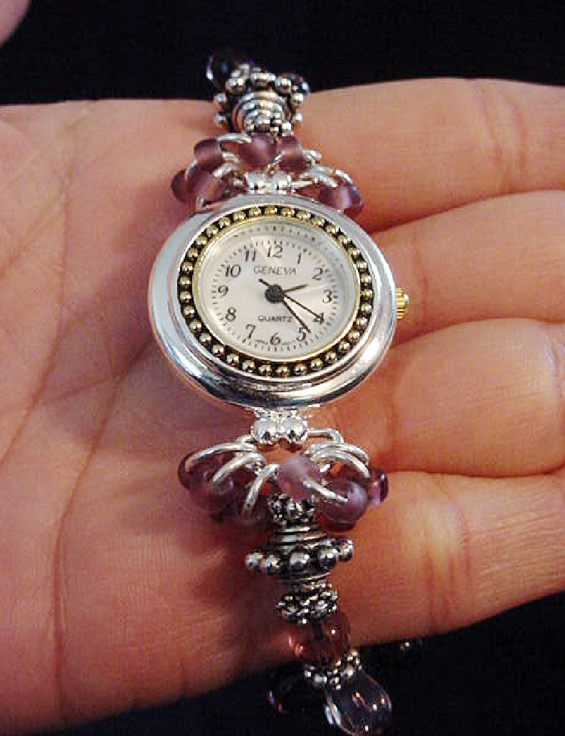 Handcrafted Jewelry Pink & Purple Watch-Handcrafted with Drop Glass Purple & Pink beads. Embellished with Silver plated  findings and details. Stretch cord is used for watch band. Round silver and gold details watch face.White Opalescent Geneva sphere. Quartz function and mechanical system. Stainless Steel back and is water resistant.Beautiful and Elegant!
