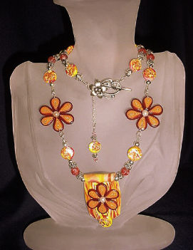 Orange and Yellow Flowery Necklace- Handmade Polymer Clay Orange and Yellow beads. Handcrafted with Sterling Silver wire, crimps, chains and findings. Beadalon .018 in/19 stringing wire is also used. Embellished with fresh water pearls, crackle beads and Austrian crystals bicone beads for final details.Beautiful and unique for that special occasion!