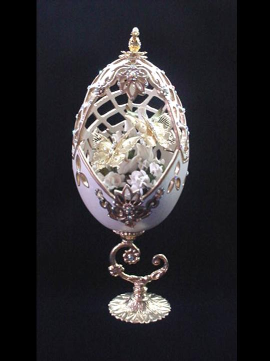 White Gala Decorated Egg (Eggypiece)-Painted in pearl ivory and gold enamel details. Accented with medium size AB Austrian Crystals. Top is movable. Completely and extremely delicate carved design. Inside, white porcelain roses embellish two gold plated butterflies. 18K gold plated stand and findings. Very Elegant! Perfect for wedding gift. Decorated box available for this decorated egg-Handmade Crafts