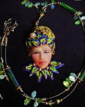 Fairy Face Green Necklace -Handmade with Polymer Clay. Findings, crimps and clasp are 14K gold plated. Gold plated Beadalon .018 in wire is also used. Glass and brass beads are used for final details. Water pearl for final detail. Unique design!