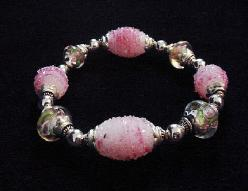 Handcrafted Jewelry Pink Glass Beads Bracelet -  Handcrafted with Pink and White  Large oval and medium round Glass beads. Transparent Lampwork pink  roses flower glass beads are used for a floral and romantic look. Embellished with Silver plated  beads and findings. Stretch cord is used for bracelet band.  Beautiful and Elegant!