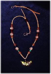 This clay handmade necklace is hand-painted in antique bronze, silver and gold. Accented w/glass beads, metal and clay handmade beads. Gold plated wire and posts are  used for final details. Unique Design and Very wild!