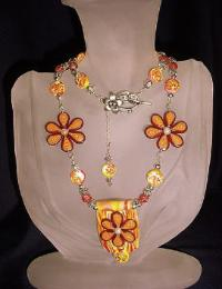 Orange and Yellow Flowery Necklace-Handmade Polymer Clay  Orange and Yellow beads.Handcrafted with Sterling Silver wire, crimps, chains and findings. Beadalon .018 in/19 stringing wire is also used.Embellished with fresh water pearls, crackle beads and Austrian crystals bicone beads for final details.Beautiful and unique for that special occasion.