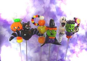 Polymer Halloween Food Picks - These unique handmade food picks will be the focal point in your party!BOO!! Handmade with polymer clay and decorated with glass beads, austrian crystals and wire. Each pick is aprox.6 in height , brass finished and washable. The set comes in a wooden handpainted base. Each set/6 comes in a clear PVC box for presentation. More seasonal designs will be available soon!