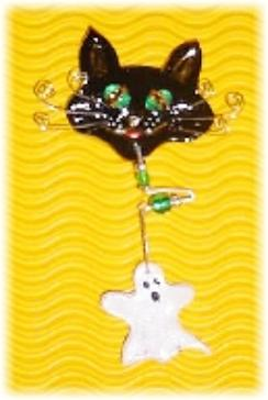 This porcelain handmade pin is painted in glossy black. Ghost is painted in pearly white. Topaz Austrian Crystals and oval shape glass beads are used for the eyes. Whiskers are made of wire. Glass and metal  beads are used for final details. Unique Design!